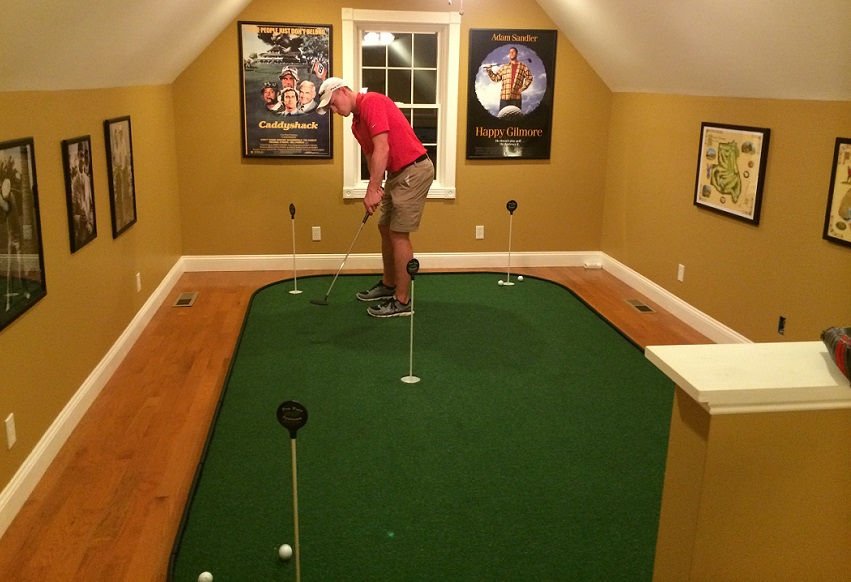 man playing on indoor putting green